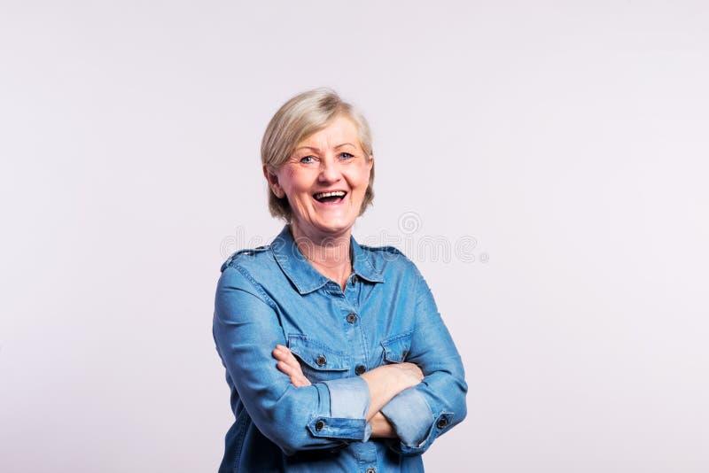 Porträt einer glücklichen älteren Frau im Studio, auf einem weißen Hintergrund lizenzfreies stockfoto
