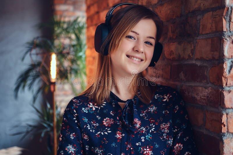 Porträt einer glücklichen bezaubernden Blondine in den Kopfhörern hörend auf m lizenzfreie stockfotos