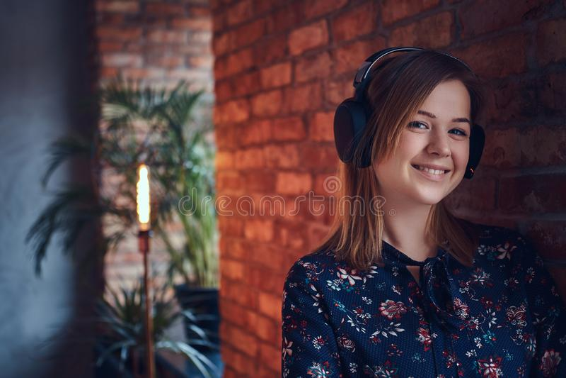 Porträt einer glücklichen bezaubernden Blondine in den Kopfhörern hörend auf m lizenzfreie stockbilder