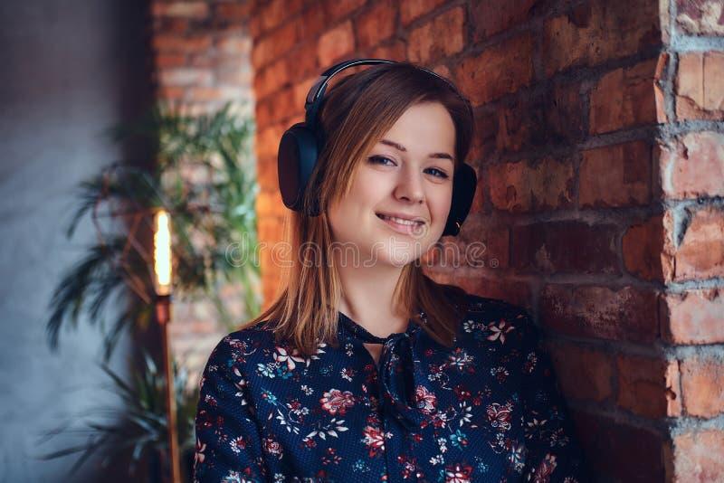 Porträt einer glücklichen bezaubernden Blondine in den Kopfhörern hörend auf m stockfotos