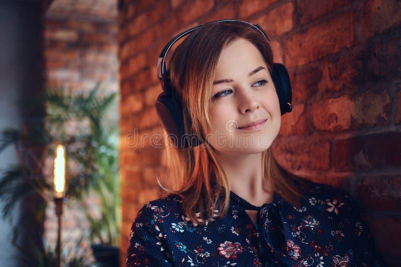 Porträt einer glücklichen bezaubernden Blondine in den Kopfhörern hörend auf m lizenzfreie stockfotografie