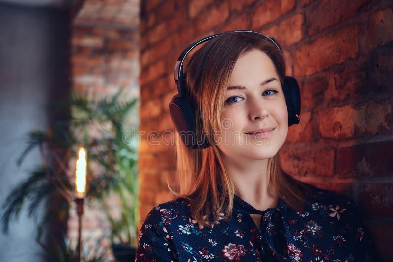 Porträt einer glücklichen bezaubernden Blondine in den Kopfhörern hörend auf m lizenzfreies stockfoto