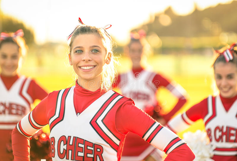 Porträt einer glücklichen jungen Cheerleader in der Aktion draußen stockfotografie