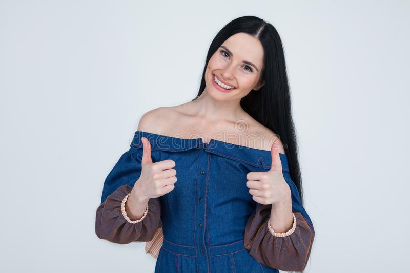 Porträt einer glücklichen jungen erfolgreichen Frau, die zwei Daumen herauf Geste in volle Ungläubigkeit lokalisiertem grauem Wan lizenzfreie stockbilder