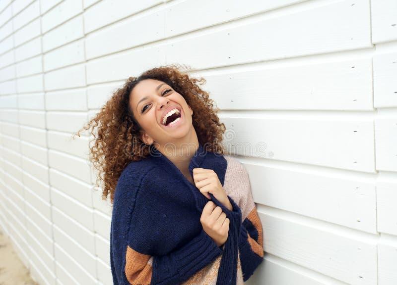 Porträt einer glücklichen jungen Frau, die Strickjacke hält und draußen lacht lizenzfreie stockfotos