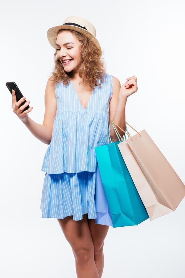 Porträt einer glücklichen jungen Frau, welche die Einkaufstaschen und Handy lokalisiert auf einem weißen Hintergrund hält lizenzfreie stockfotos