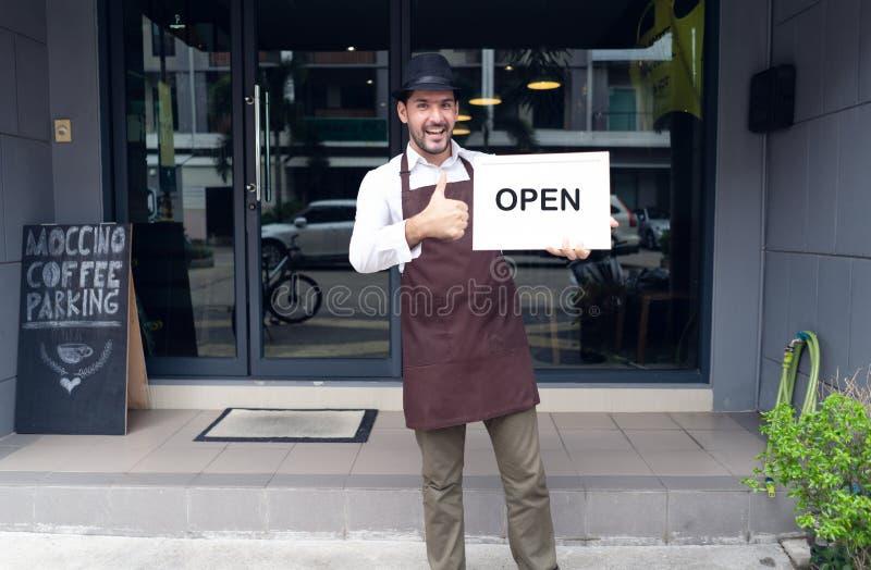 Porträt einer glücklichen Kellnerinstellung am Kaffeestubeeingang und des Haltens des offenen Zeichens in der vorderen Kaffeestub stockbild