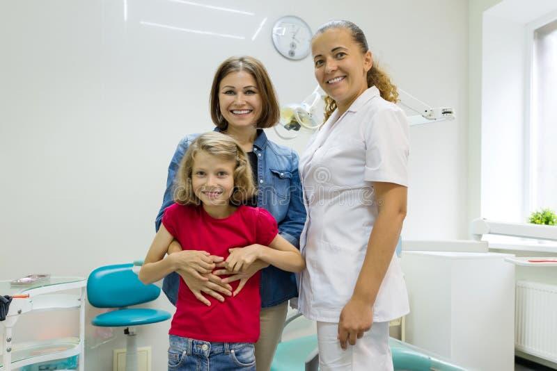 Porträt einer glücklichen Mutter mit Kind und Doktorzahnarzt, im zahnmedizinischen Büro lizenzfreies stockfoto