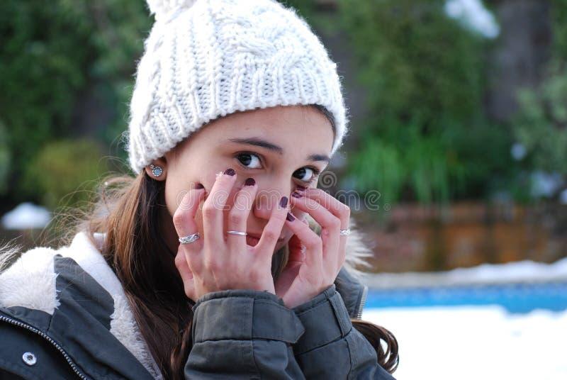 Porträt einer glaubenden Kälte des Jugendlichmädchens mit einem Wollhut lizenzfreie stockfotografie
