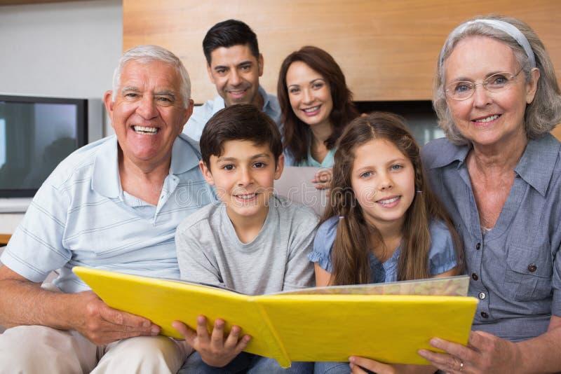 Porträt einer Großfamilie, die ihr Albumfoto betrachtet stockfotografie