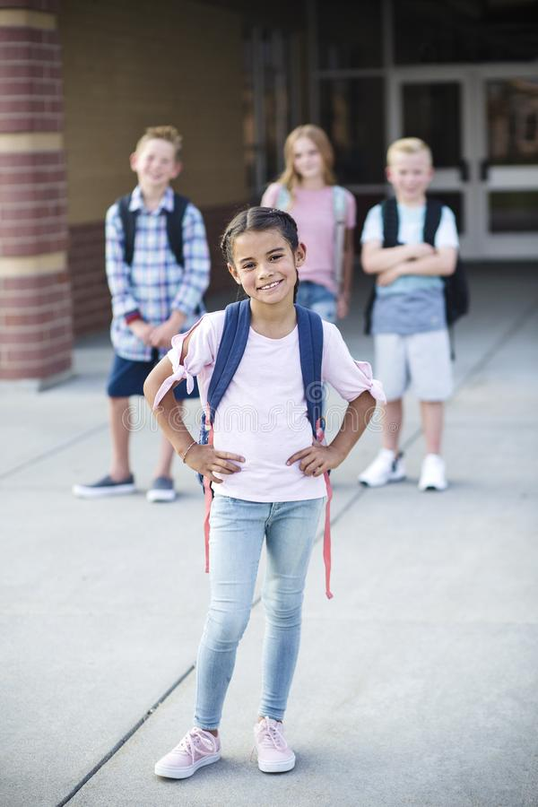 Porträt einer Gruppe lächelnder Grundschüler mit Rucksäcken lizenzfreie stockfotografie
