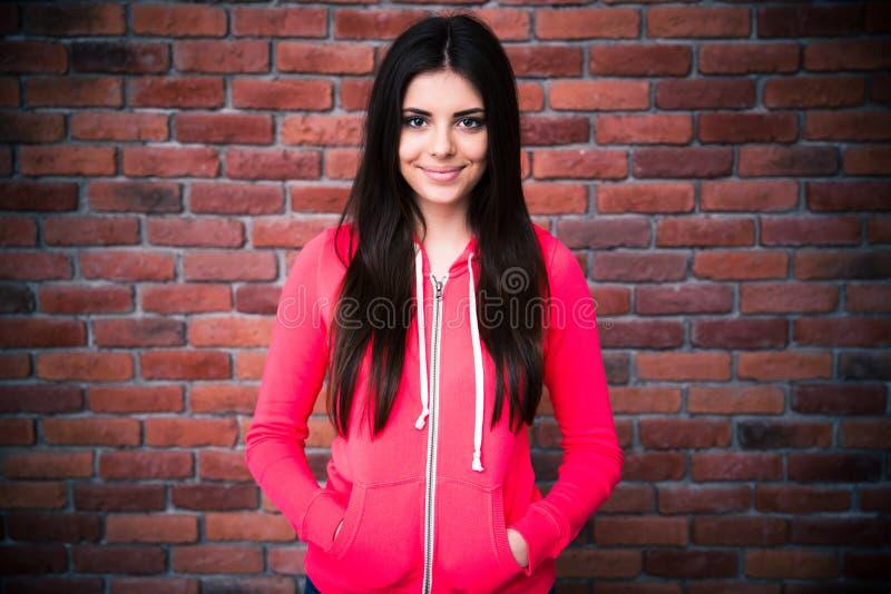 Porträt einer hübschen Frau über Backsteinmauer stockfotografie