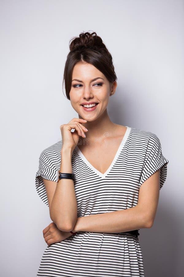 Porträt einer hübschen lächelnden Frau, die auf einem weißen Hintergrund aufwirft lizenzfreies stockfoto
