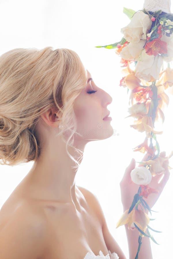 Porträt einer herrlichen, jungen Braut mit Blumen stockbilder