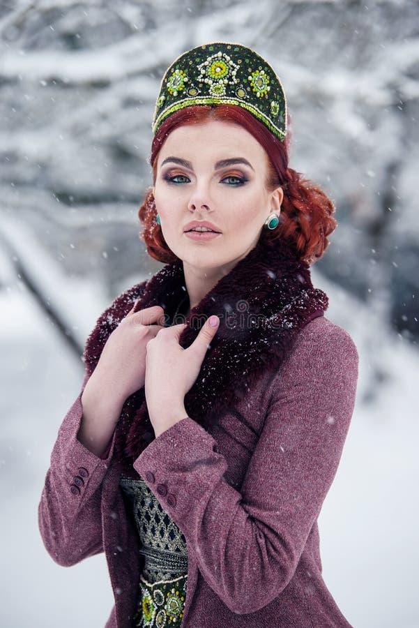 Porträt einer herrlichen jungen Frau im russischen Artkleid auf einem starken Frost an einem schneebedeckten Tag des Winters Russ stockbilder