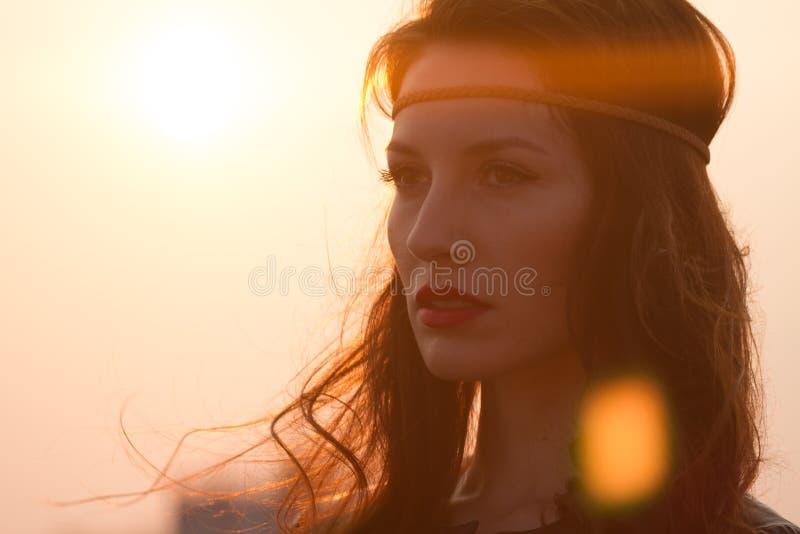 Porträt einer Hippiefrau mit dem Stirnband, das weit weg Sonnenuntergang mit dem windigen Haar betrachtet stockbilder