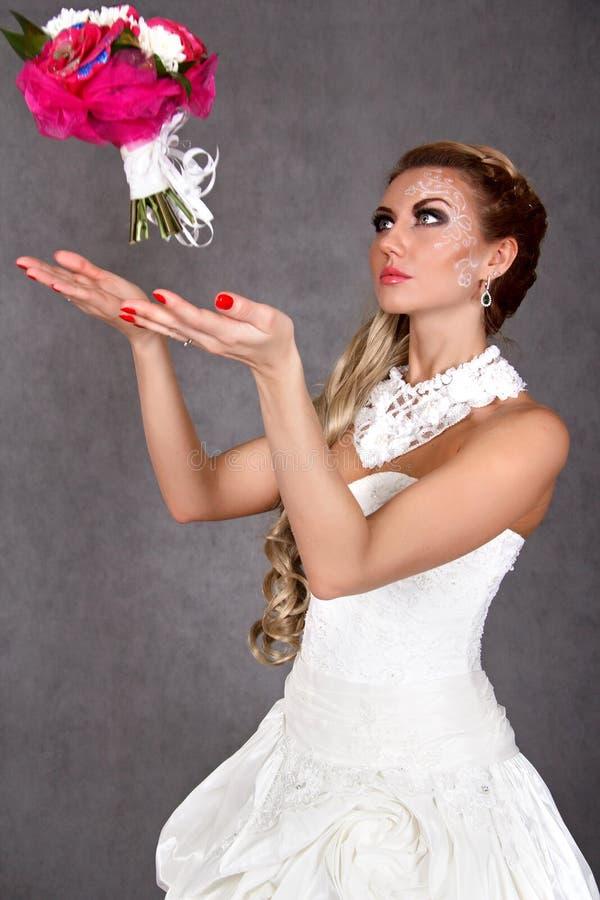 Porträt einer jungen attraktiven Braut, die einen Blumenstrauß wirft lizenzfreie stockfotografie