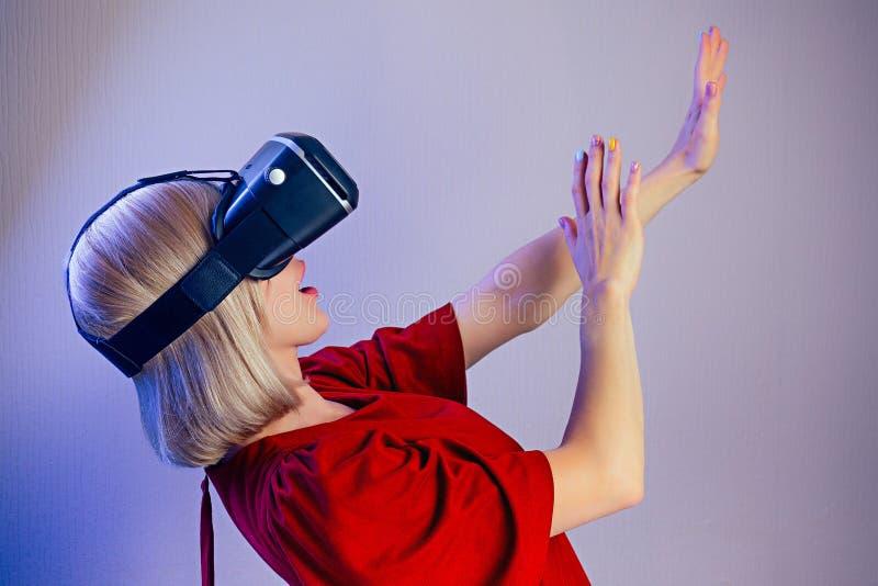 Porträt einer jungen attraktiven erstaunt Frau mit blondem Haar in der Helmbrille der virtuellen Realität schockiert und schockie stockfotografie