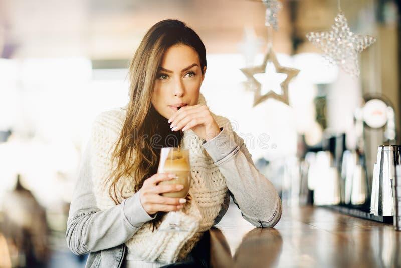 Porträt einer jungen, attraktiven Frau, allein sitzend an einer Bar, trinkender Kaffee lizenzfreie stockbilder