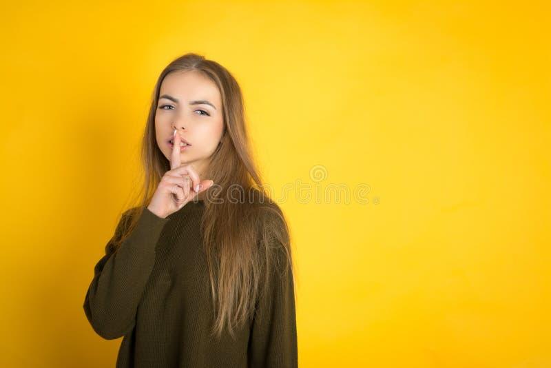 Porträt einer jungen attraktiven Frau mit dem langen Haar und Make-up hält einen Finger nahe den Lippen im Studio auf einem Gelb lizenzfreie stockfotos