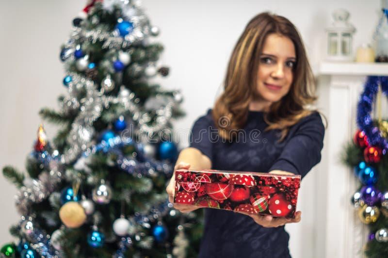 Porträt einer jungen, attraktiven und fotogenen lächelnden Frau, da sie einen Kasten hält, den sie für ein Geschenk empfing Sie s stockfotografie