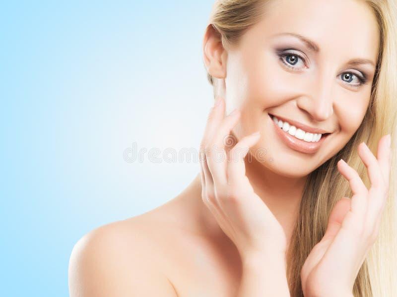Porträt einer jungen blonden Frau im Make-up auf einem blauen Hintergrund stockbilder