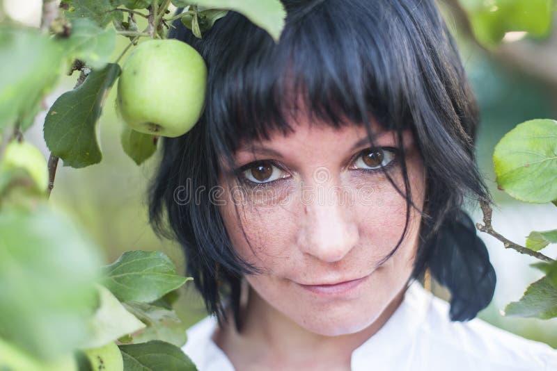 Porträt einer jungen dunkelhaarigen Frau unter dem Apfelbaum im Garten stockfotografie