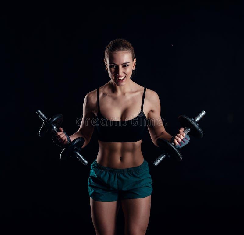 Porträt einer jungen Eignungsfrau in der Sportkleidung, die Training mit Dummköpfen auf schwarzem Hintergrund tut Gebräuntes sexy stockbilder