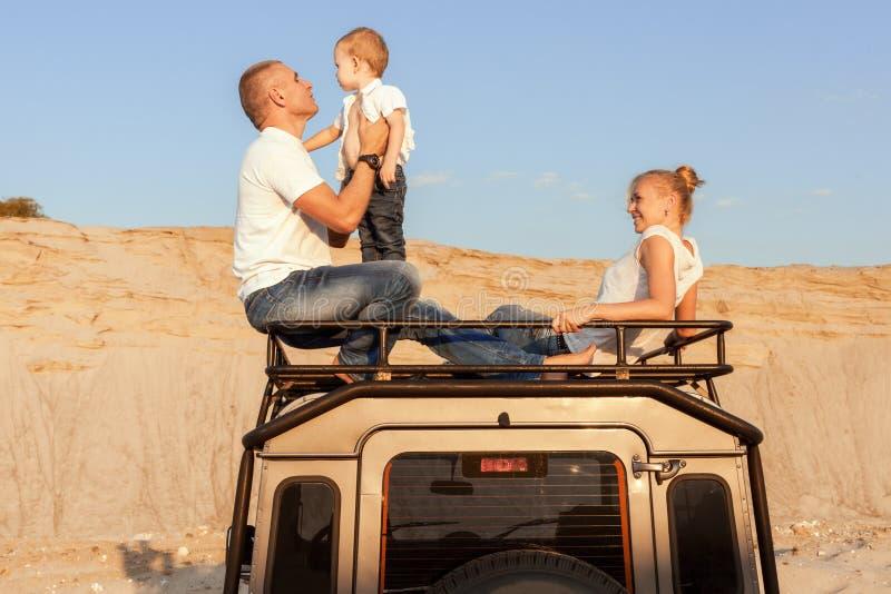 Porträt einer jungen Familie auf dem Autodach lizenzfreie stockfotografie