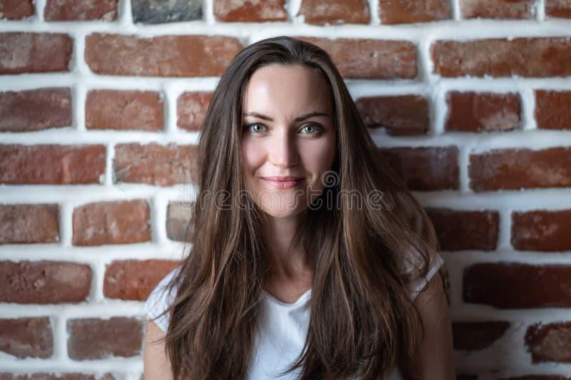 Porträt einer jungen Frau auf einem Wandhintergrund des roten Backsteins stockfotos
