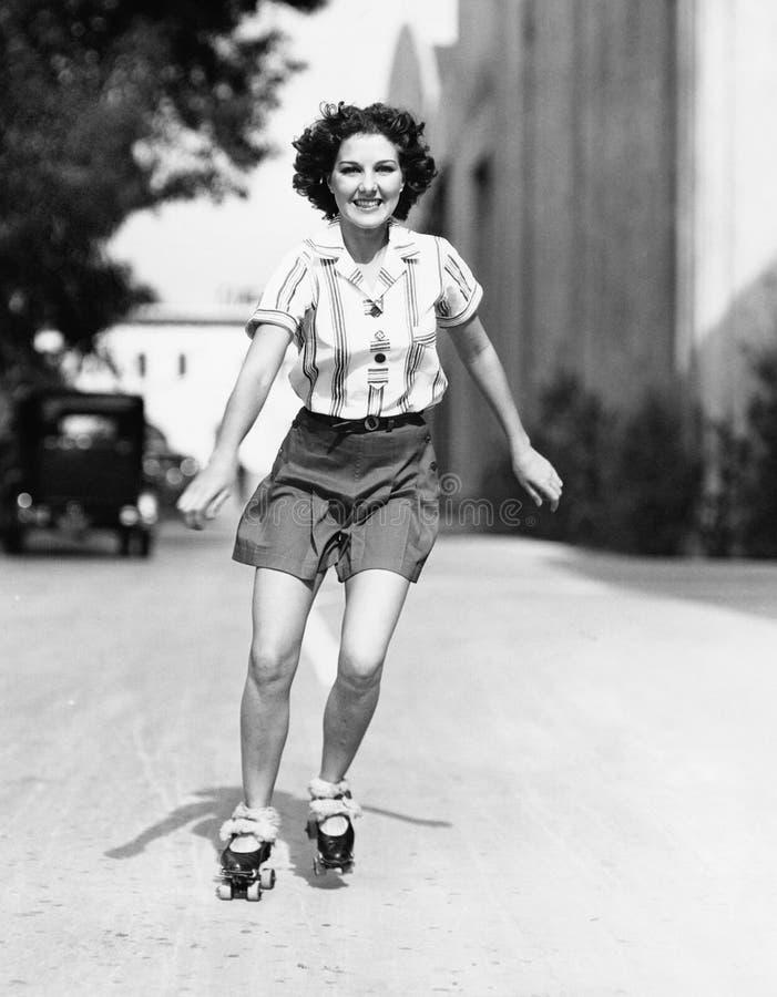 Porträt einer jungen Frau, die auf die Straße eisläuft und Lächeln (alle dargestellten Personen sind nicht längeres lebendes und  stockbilder