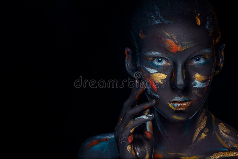 Porträt einer jungen Frau, die aufwirft, bedeckte mit schwarzer Farbe stockfotos