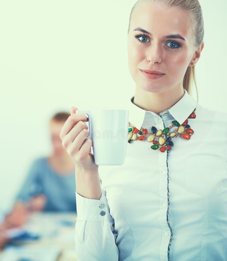 Porträt einer jungen Frau, die an der Bürostellung arbeitet lizenzfreie stockfotografie