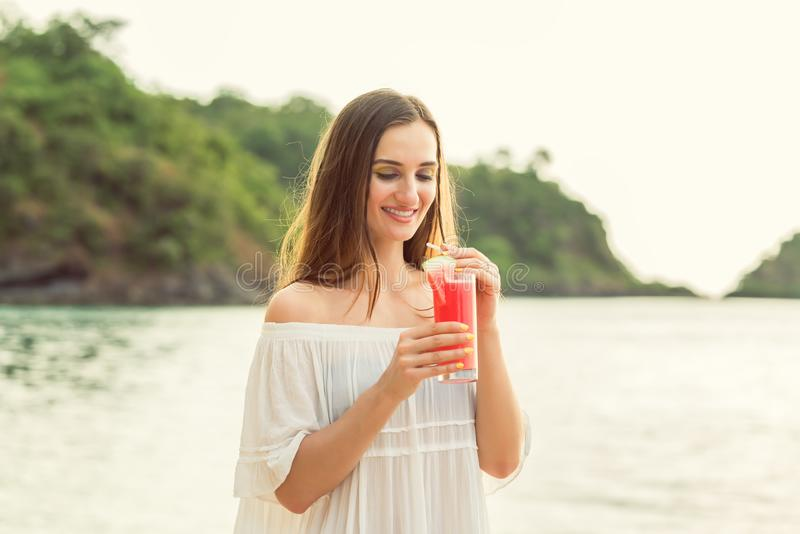 Porträt einer jungen Frau, die ein frisches Wassermelonencocktail auf tropischem Strand hält lizenzfreie stockbilder