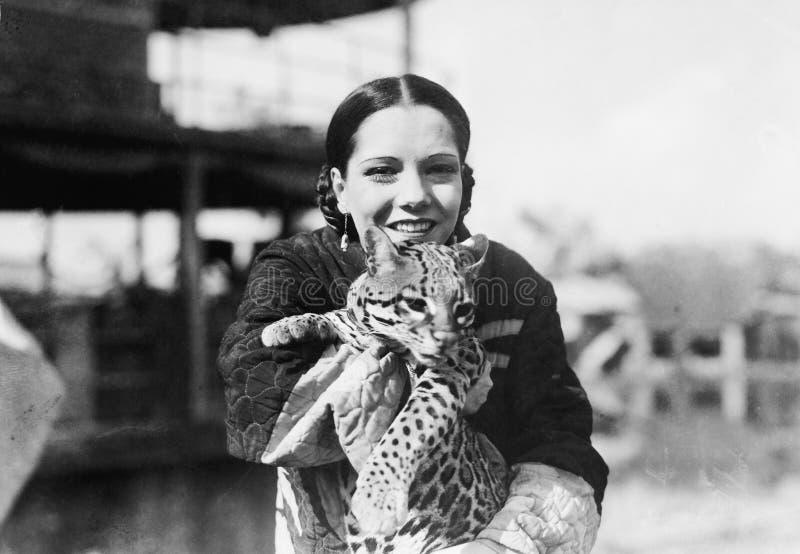 Porträt einer jungen Frau, die ein Gepardjunges trägt und Lächeln (alle dargestellten Personen sind nicht längeres lebendes und k stockfoto