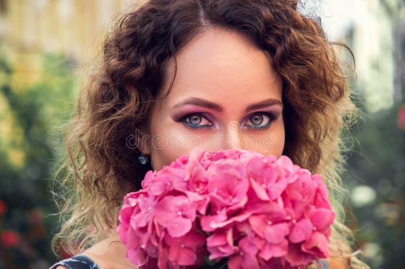 Porträt einer jungen Frau, die eine große rosa Hortensie schnüffelt Mysteriöser Blick geschickt zur Kamera lizenzfreie stockfotografie