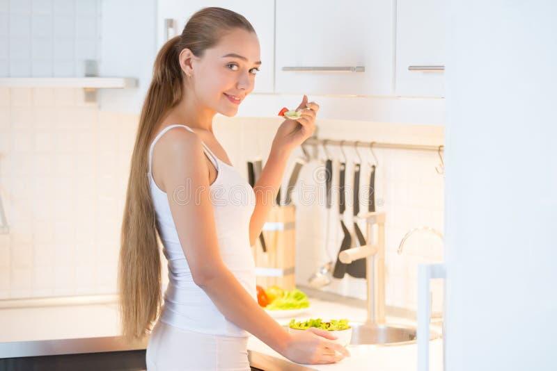 Porträt einer jungen Frau, die einen grünen Salat auf der Küche schmeckt, lizenzfreie stockfotografie