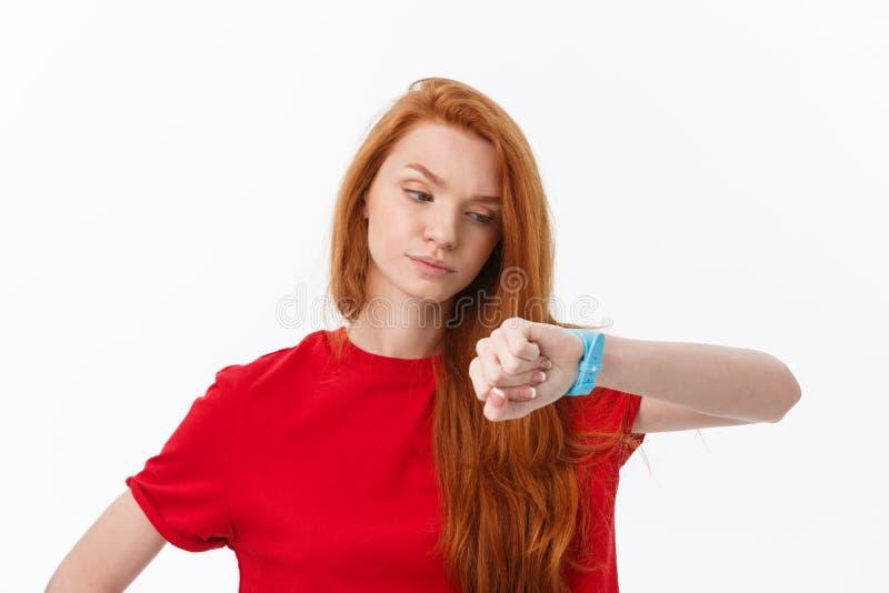Porträt einer jungen Frau, die Finger auf der Armbanduhr lokalisiert auf einem weißen Hintergrund zeigt stockfotografie