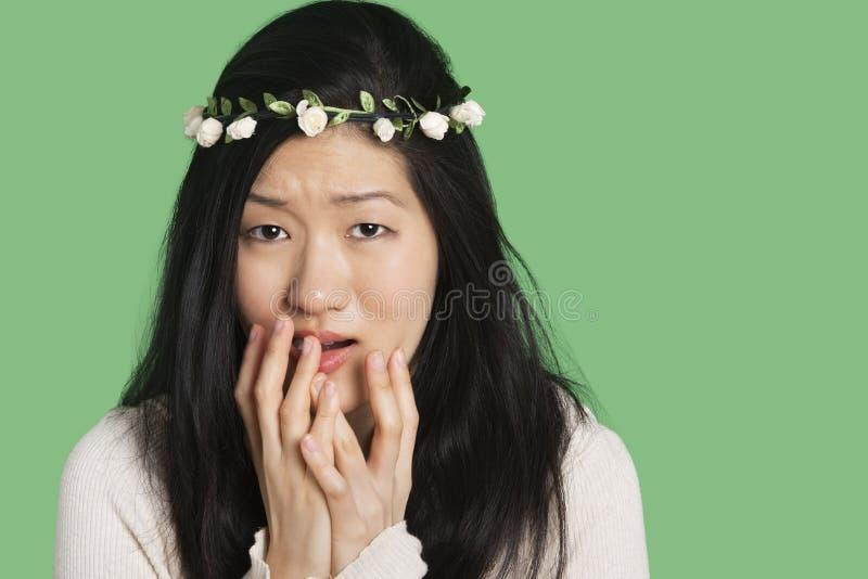 Porträt einer jungen Frau, die Furcht und Angst über grünem Hintergrund ausdrückt lizenzfreie stockfotos