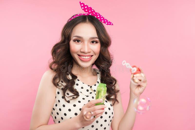 Porträt einer jungen Frau, die mit Seifenblasen über rosa Ba spielt lizenzfreies stockfoto