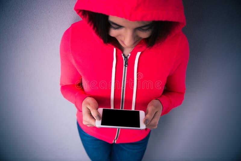 Porträt einer jungen Frau, die mit Smartphone steht stockfotos