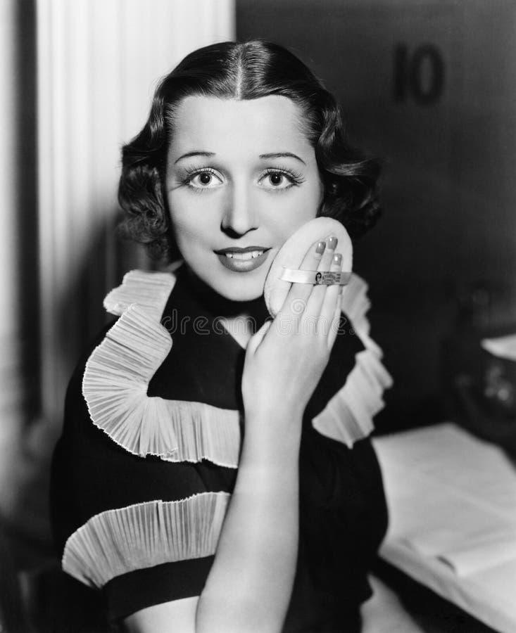 Porträt einer jungen Frau, die Pulver an ihrem Gesicht anwendet (alle dargestellten Personen sind nicht längeres lebendes und kei lizenzfreie stockfotografie
