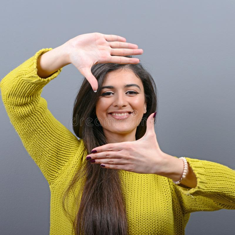 Porträt einer jungen Frau, die Rahmen mit den Händen gegen grauen Hintergrund macht lizenzfreie stockbilder