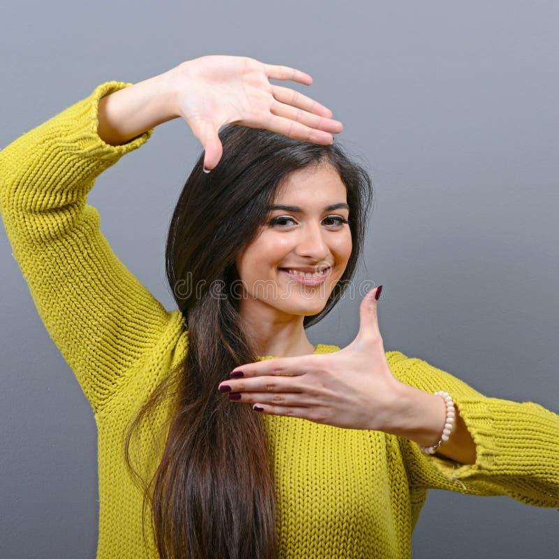 Porträt einer jungen Frau, die Rahmen mit den Händen gegen grauen Hintergrund macht lizenzfreie stockfotos