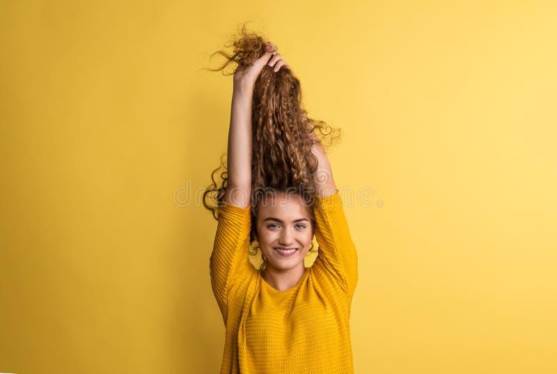 Porträt einer jungen Frau in einem Studio auf einem gelben Hintergrund, Spaß habend lizenzfreie stockfotos