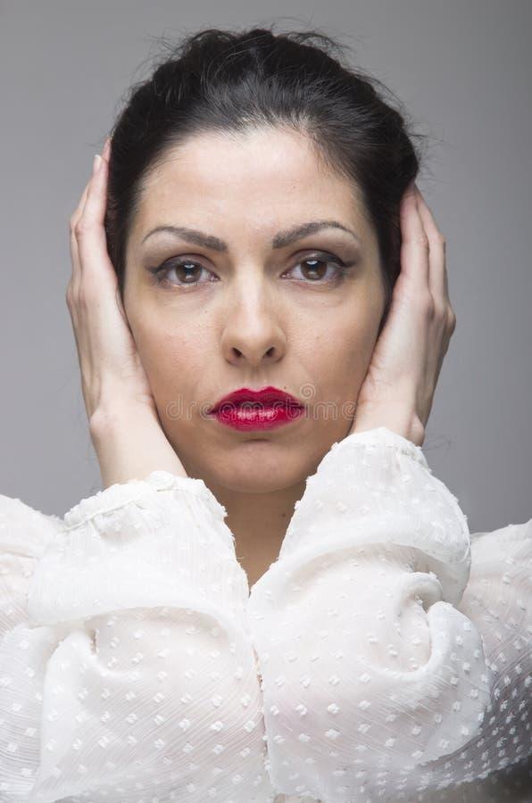 Porträt einer jungen Frau gegen einen grauen Hintergrund stockfotografie