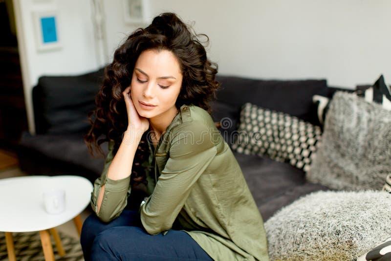 Porträt einer jungen Frau mit dem gelockten Haar entspannt sich auf einem Sofa in t stockbilder