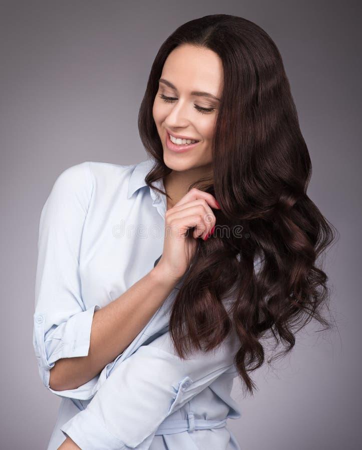 Porträt einer jungen Frau mit dem langen schönen Haar Make-up und ein helles Lächeln stockfotos