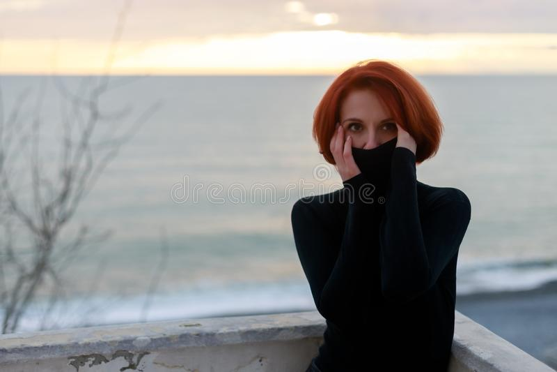 Porträt einer jungen Frau mit dem roten Haar mit einem rastlosen Blick auf dem Hintergrund des Meeres und des Sonnenuntergangs im lizenzfreie stockfotografie
