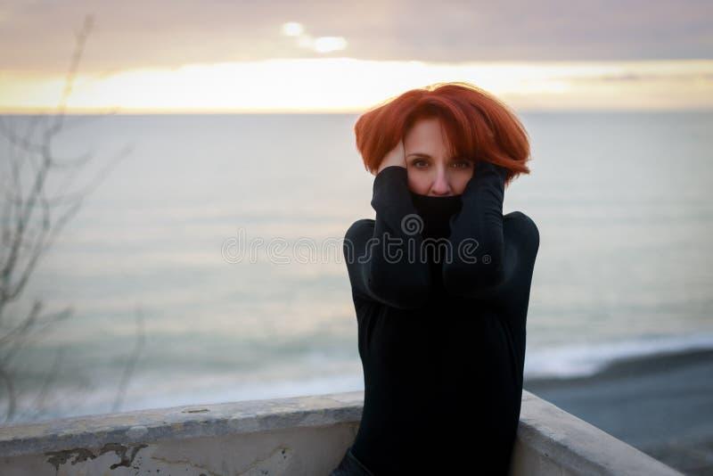 Porträt einer jungen Frau mit dem roten Haar und des durchbohrenden Blickes auf dem Hintergrund des Meeres und des Sonnenuntergan lizenzfreie stockfotos